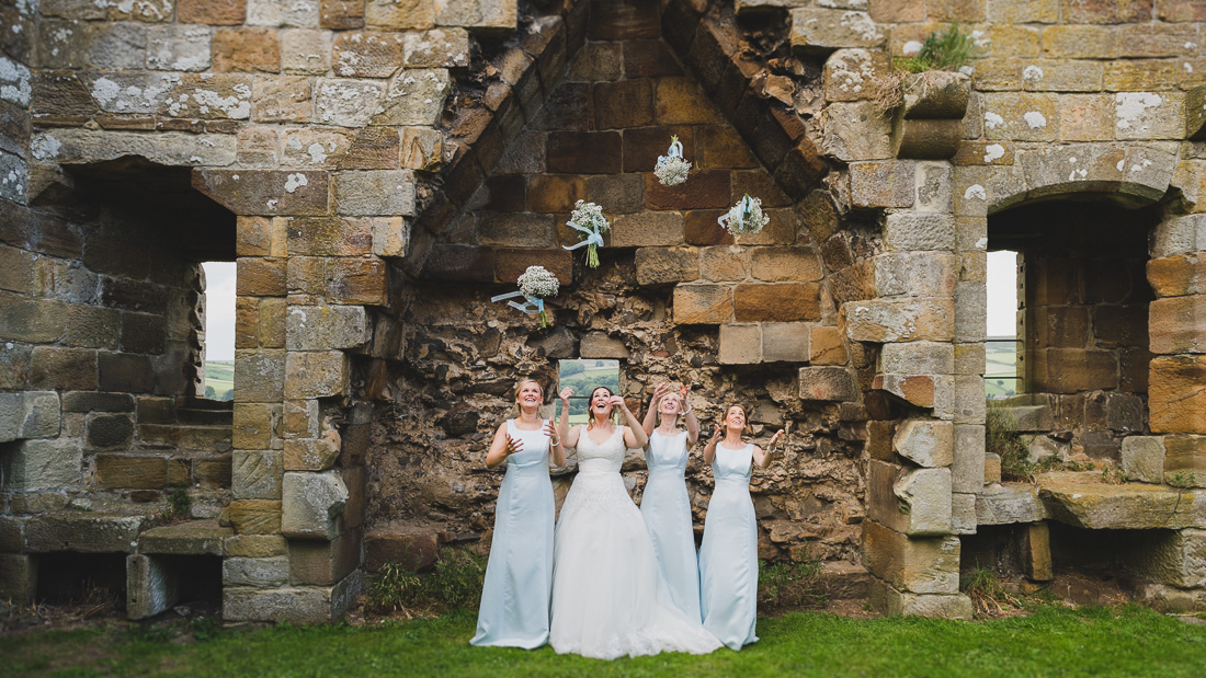 Bride and Bridesmaids throwing flowers Danby Castle Wedding